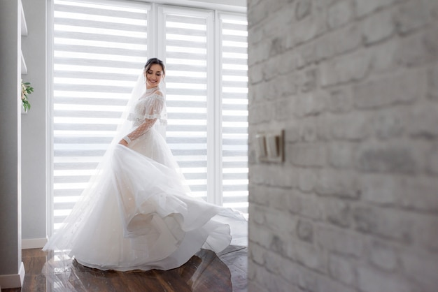 Smiled pretty bride is turning around in room near white brick wall dressed in fashionable dress, wedding fashion