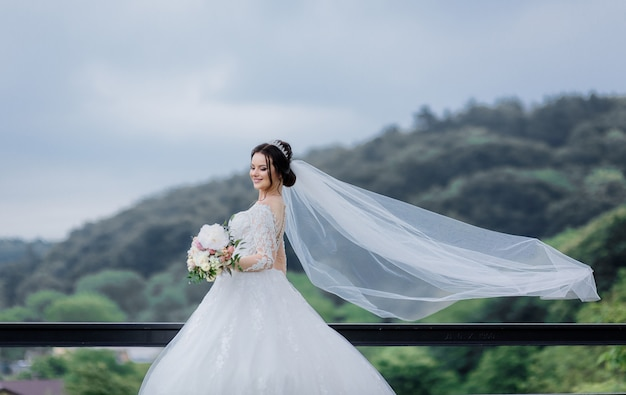 Smiled pretty caucasian bride with long veil outdoors holding wedding bouquet