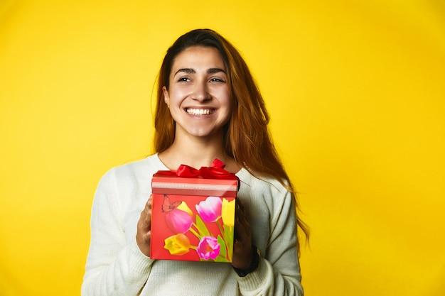 Улыбчивая рыжая кавказская девушка держит в руках красный подарок с возбужденным лицом