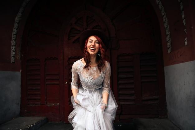 古いバーガンディのドアの近くのライトグレーのドレスに身を包んだバーガンディの髪の笑顔の女性