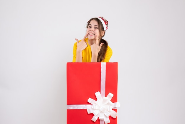 Smiled young girl with santa hat standing behind big xmas gift on white
