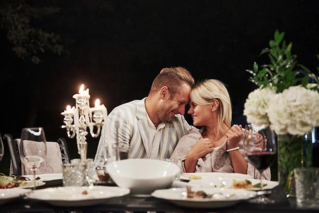 笑顔と幸せを感じます。美しい大人のカップルは夜の時間に豪華なディナーを持っています