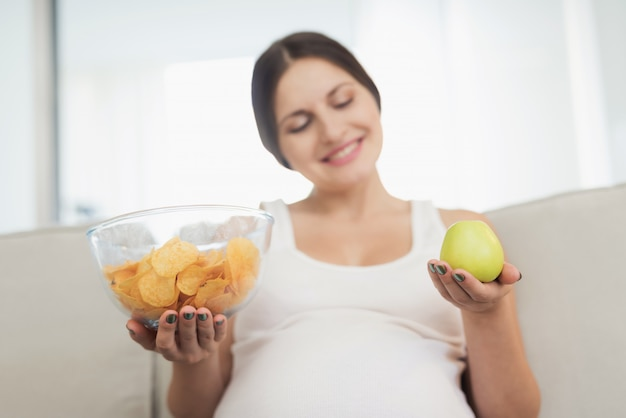 Smiles woman. belly choose apple or vase of chips.