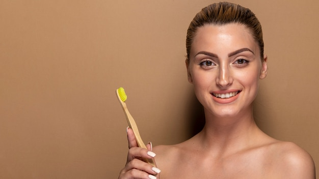 Smiley adult woman holding toothbrush