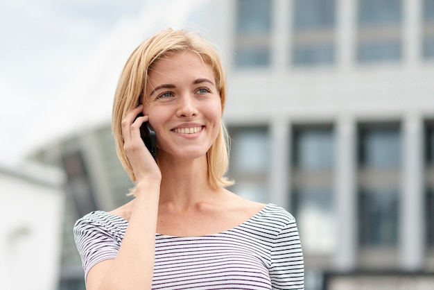 Smiley adult woman talking on the phone