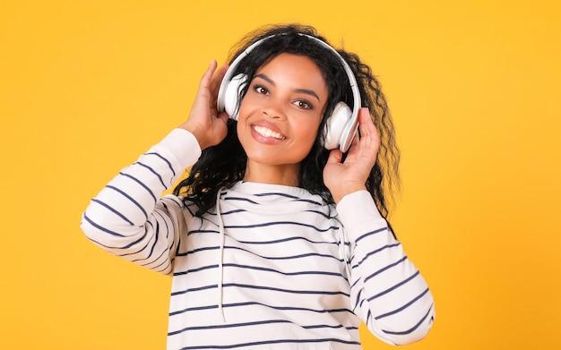 줄무늬 후드티를 입은 웃는 아프리카계 미국인 여성이 노란색 배경 위에 포즈를 취하고 머리에 흰색 이어폰을 들고 카메라를 바라보고 있습니다