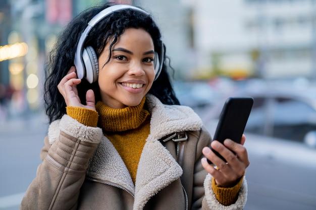 ヘッドフォンで音楽を聴いているスマイリーアフリカ系アメリカ人の女性
