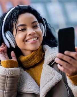 屋外で音楽を聴いているスマイリーアフリカ系アメリカ人の女性