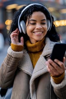 外で音楽を聴いているスマイリーアフリカ系アメリカ人の女性