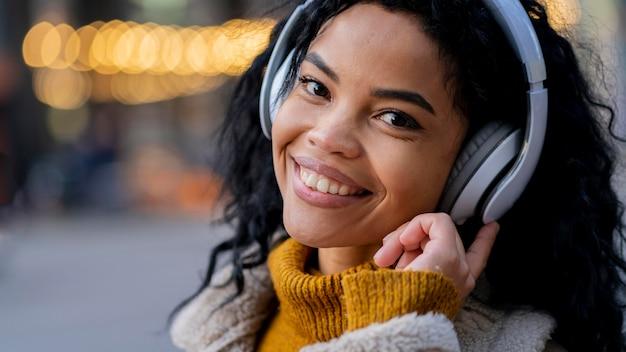 音楽を聴いているスマイリーアフリカ系アメリカ人の女性