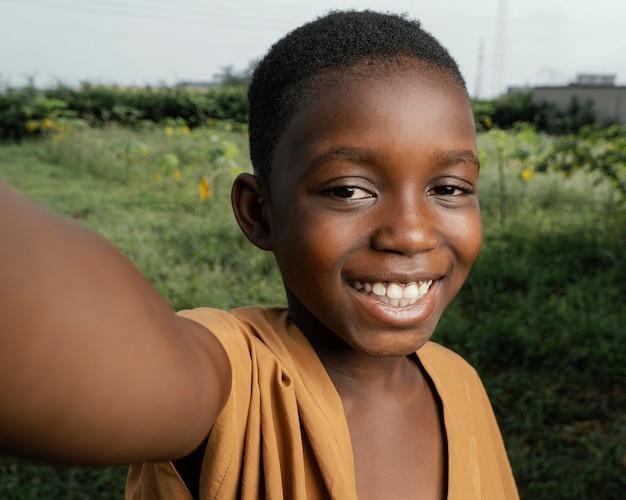 緑のフィールドでスマイリーアフリカの子供