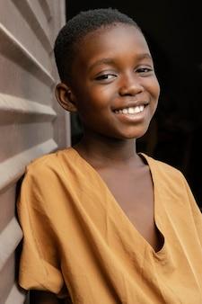 壁の横にポーズをとるスマイリーアフリカの子供
