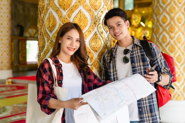 Smiley asian couple tourist backpackers standing in beautiful thai temple, pretty woman holding paper map and handsome man check in smartphone with happy on vacations