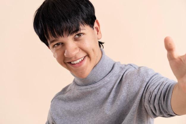 Смайлик азиатский мужчина с карликовостью позирует
