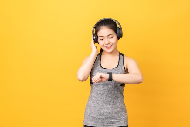 オレンジ色の壁にスマートウォッチとヘッドフォンを探しているスポーツウェアを着てスマイリーアジアの女性