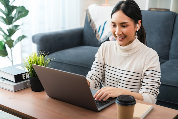 Smiley asian young woman using a laptop at the table, study online on the internet and video call with teachers and friends.