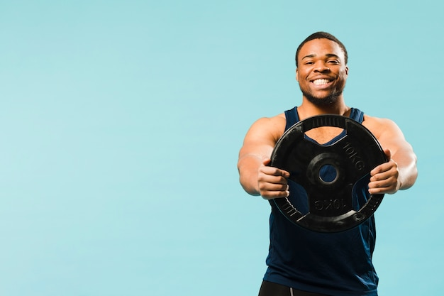 Smiley athlete holding weights with copy space