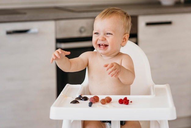 Smiley baby in highchair choosing what fruit to eat