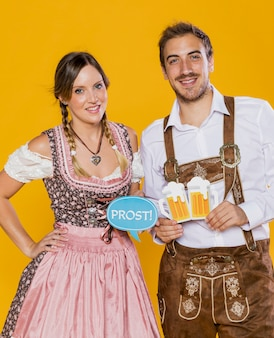 Smiley bavarian couple holding oktoberfest signs