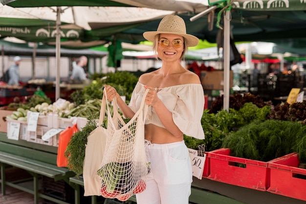 채소의 전체 가방을 들고 웃는 아름 다운 여자