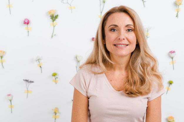 Smiley beautiful woman with floral wall
