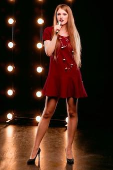 カラオケのステージでマイクの歌を歌う笑顔の美しい女性