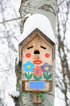Смайлик-скворечник. скворечник в виде забавной мордочки на дереве. деревянный скворечник ручной работы, покрытый снегом. зимний пейзаж с деревьями, покрытыми снегом и копией пространства.