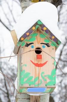 Смайлик-скворечник. скворечник в виде забавной мордашки на дереве. деревянный скворечник ручной работы, покрытый снегом. зимний пейзаж с деревьями, покрытыми снегом и копией пространства.