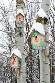 Smiley birdhouses. birdhouse in the form of a funny face on the tree. handmade wooden nesting box covered in snow. winter landscape with trees covered of the snow and copy space.