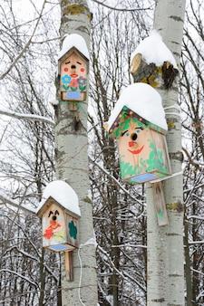 Смайлик-скворечники. скворечник в виде забавной мордашки на дереве. деревянный скворечник ручной работы, покрытый снегом. зимний пейзаж с деревьями, покрытыми снегом и копией пространства.