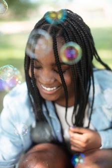 シャボン玉で遊ぶスマイリー黒の10代の少女