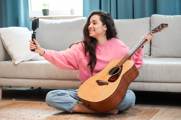 Smiley blogger smiling and recording herself with her guitar