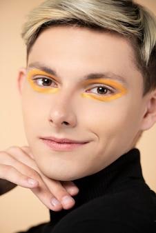 Uomo biondo di smiley che porta eyeliner arancione