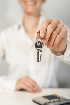 Smiley blurred woman holding house keys