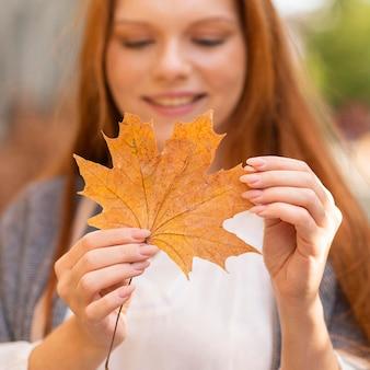 スマイリーぼやけて葉を保持している女性