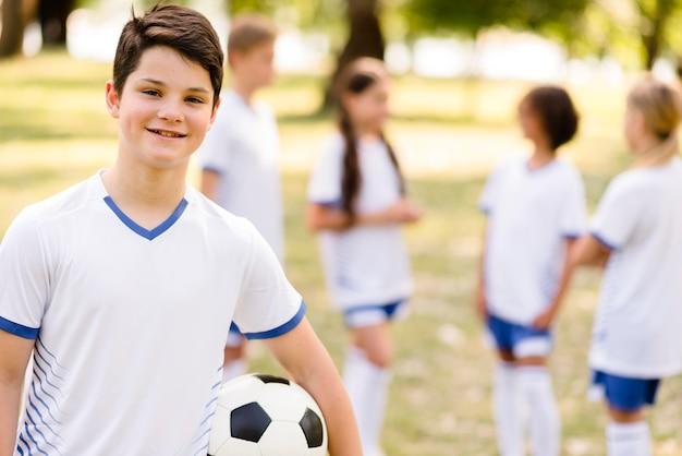 Улыбающийся мальчик держит футбольный мяч рядом со своими товарищами по команде