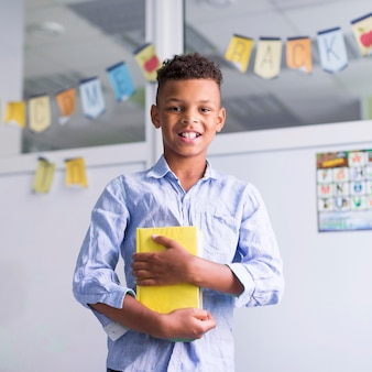 Smiley boy holding a book in class