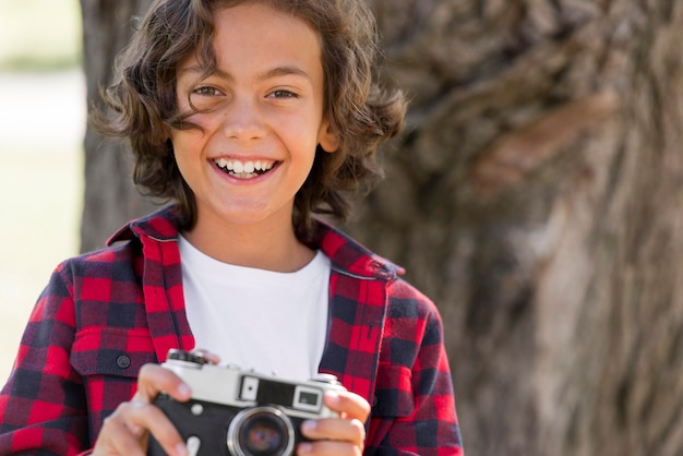 Смайлик мальчик держит камеру в парке