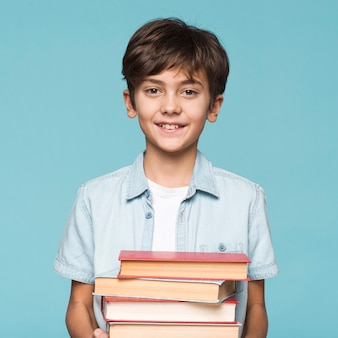 Smiley boy holding stack of books