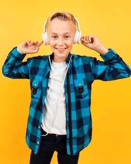 Smiley boy listening music at headphones