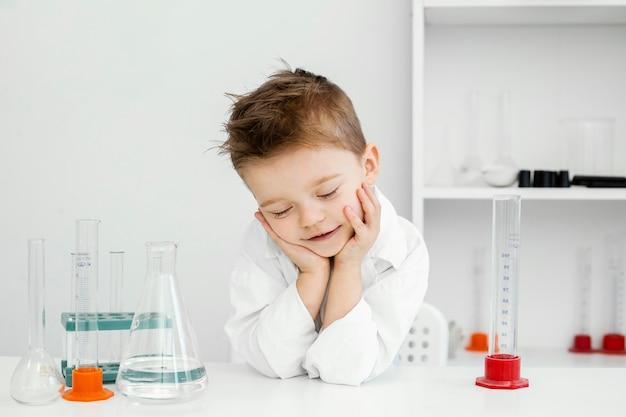 科学について学ぶ試験管を持つ実験室のスマイリー少年科学者