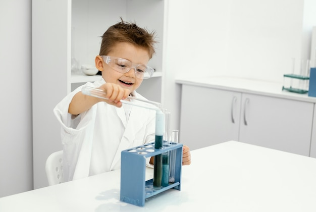 Smiley boy scientist in the laboratory with test tubes doing experiments