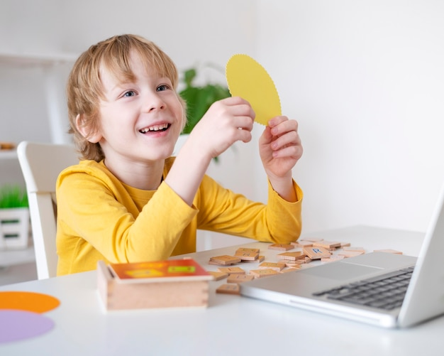 집에서 노트북을 사용 하여 웃는 소년