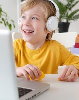 Ragazzo di smiley utilizzando laptop e cuffie a casa