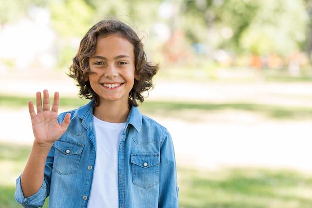 Улыбающийся мальчик машет рукой в парке