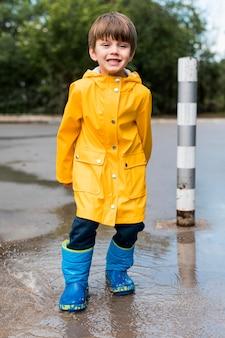 Ragazzo sorridente che indossa abiti da pioggia