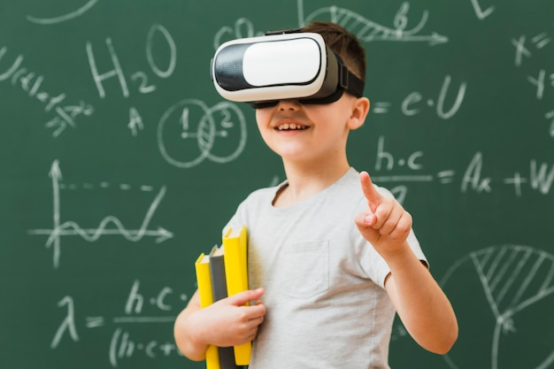 Smiley boy wearing virtual reality headset and holding books