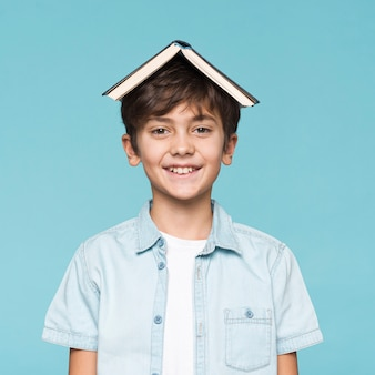 Smiley boy with book on head