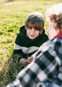 야외 잔디에 그의 친구와 함께 웃는 소년