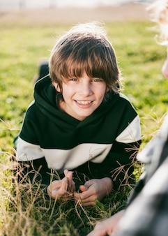 잔디에 그의 친구와 함께 웃는 소년